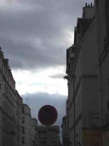 Panneau stationnement interdit dans une rue de Paris sous un ciel d'orage